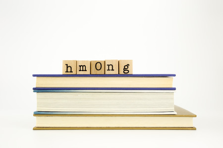 thai language: hmong word on wood stamps stack on books, academic and language concept