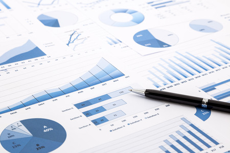 pen on blue charts, graphs, data and reports background for education and business concepts