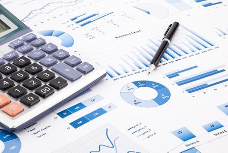 rekenmachine en pen met blauwe zakelijke grafieken, grafieken, infomatie en rapporten achtergrond voor financiële en zakelijke concepten