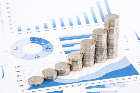 closeup stapels Thaise baht munten op blauwe grafieken en diagrammen achtergrond, geld en financiële begrippen Stockfoto