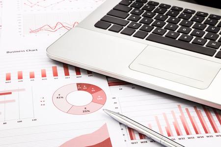administracion de empresas: portátil y pluma con gráficos de negocios de color rojo, gráficos, infomación y los informes de antecedentes de los conceptos financieros y empresariales Foto de archivo