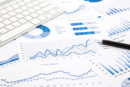 probability: closeup blue graph and chart reports with white keyboard and pen on office table, financial and business concept