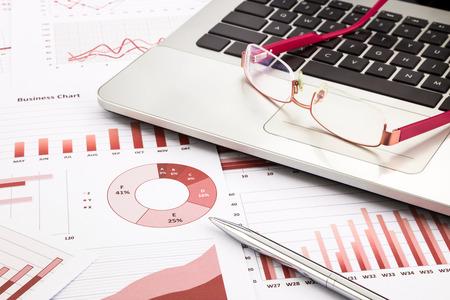 administracion de empresas: ordenador portátil y gafas con gráficos de negocios, gráficos, informes de investigación y fondo rojo para gestión y conceptos de negocio Foto de archivo