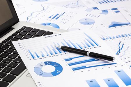 informe: portátil y pluma con gráficos de negocios de color azul