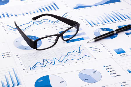 conclude: glasses and pen on blue charts Stock Photo