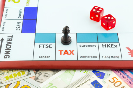 money background and stock exchange board game with red dices and black piece places on tax area