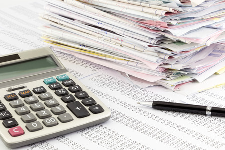 calculator and invoices on financial summary report