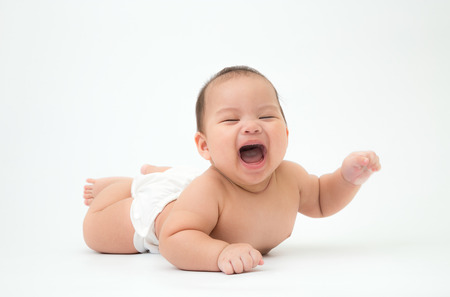 lively: happy laughing child lies on stomach, 5 months old asian baby boy Stock Photo