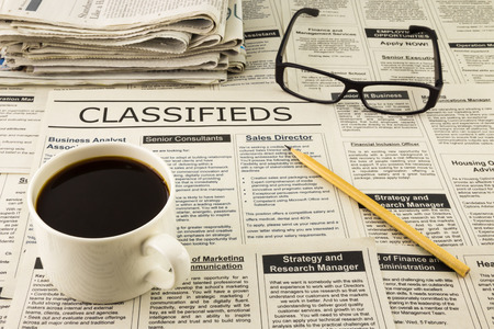classifieds: classifieds ads on newspaper place on table with glasses, pencil and a cup of coffee
