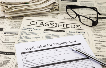blank job application form place on classifieds ads with stack of newspaper and glasses