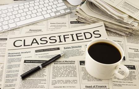 キーボード、ペン、コーヒーのカップを持つテーブル上の新聞ディスプレイ クラシファイド広告場所 写真素材