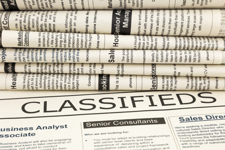 classifieds: close up stack of newspapers, focus on classifieds word