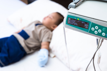 dehydration: sick baby receiving intravenous therapy in hospital, focus on infusion pump