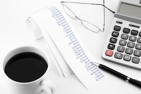 cuadro sinoptico: concepto de contabilidad con el resumen de comprar rollos de papel en la mesa de la oficina en tono blanco Foto de archivo