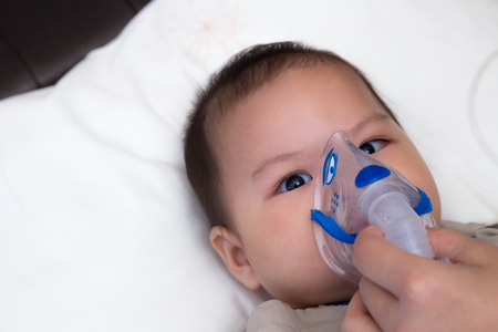 5 months old baby with respiratory disease, inhaling medication through spacer while laying in hospital bed Stock Photo