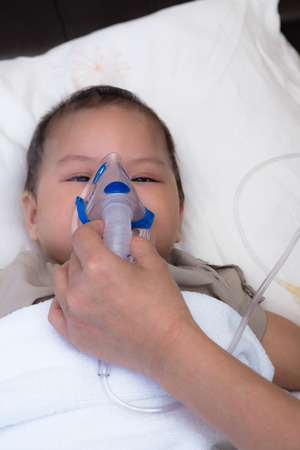 5 months old baby with respiratory syncytial virus, inhaling medication through spacer while laying in hospital bed photo