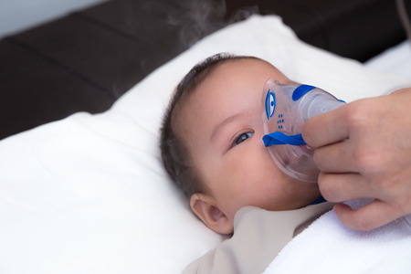 5 months old baby with respiratory syncytial virus, inhaling medication through inhalation mask while looking at with his tired eyes