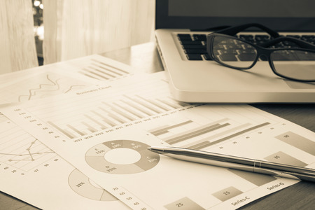 Budget planning and financial summary reports with graphs and charts place on home office table