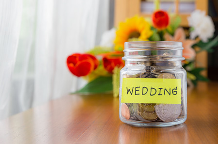 Veel wereld munten in een pot met geld bruiloft etiket op kruik, mooie bloemen op de achtergrond