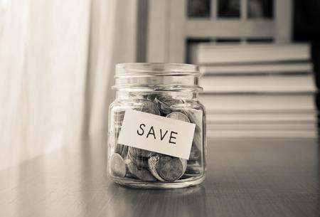 Un pot de l'argent de l'épargne avec des pièces du monde et d'économiser mot sur l'étiquette ou tag, noir et blanc image Banque d'images - 32565096