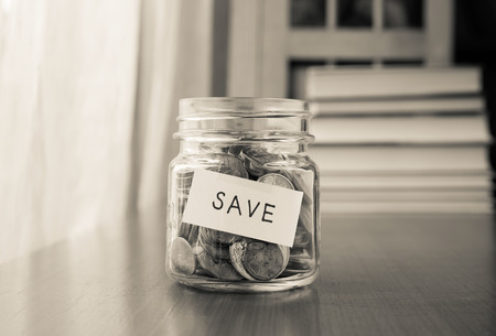 A savings money jar with world coins and save word on label or tag, black and white image Foto de archivo