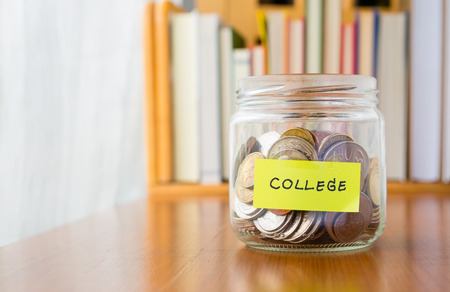 colegios: Muchas monedas del mundo en ahorro de dinero frasco con etiqueta de la universidad en el tarro, el concepto de planificaci�n financiera para los ni�os Foto de archivo