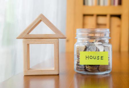 多くの世界のコインをガラス銀行テーブルの上の単語またはお金の瓶と木製ホーム幾何学ブロックのラベルを家します。 写真素材