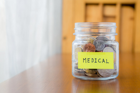 Glass bank with many world coins and  medical word or label on saving money jar 写真素材
