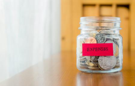 Glas bank met vele wereld munten en uitgaven woord of etiket op het besparen van geld jar Stockfoto