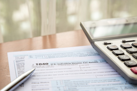income tax: Form 1040, U.S. Individual income tax return place on table with calculator and pen Stock Photo