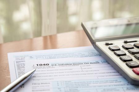 ingresos: Formulario 1040, US Individual lugar la declaraci�n de impuestos en la mesa con la calculadora y la pluma Foto de archivo