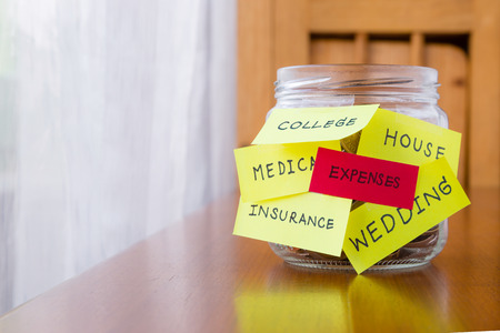 A jar of coins with expenses and other words or labels on savings money jar