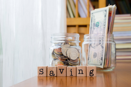 Saving word on rubber stamps place on table with coins and banknotes in money jars, concept to personal finance Banco de Imagens