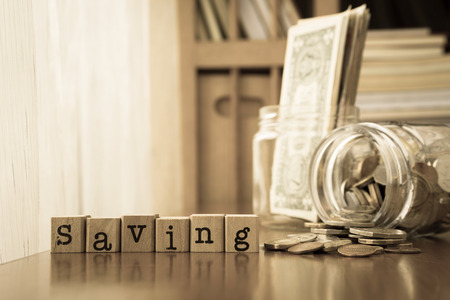 Saving word on rubber stamps place on table with coins and banknotes in money jars, sepia toning