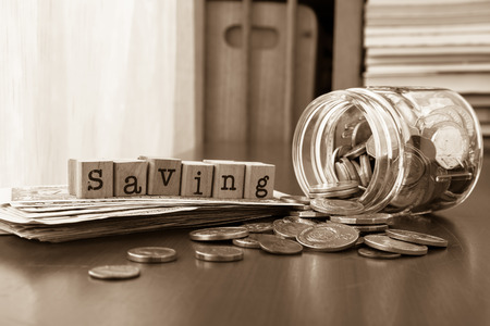 Saving word on rubber stamps place on banknotes with coins spilling out of money jars, sepia toned