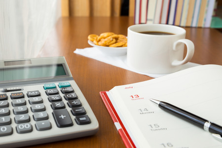 Blank timetable or calendar place on table with calculator and coffee break