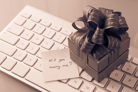 will you marry me: Gift box and paper note with romantic love message: Will you marry me? place on keyboard, valentines day concept, Sepia toned
