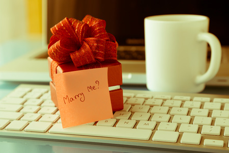 will you marry me: Gift box and sticky note with romantic love message: Will you marry me? place on keyboard, valentines day concept, retro image style