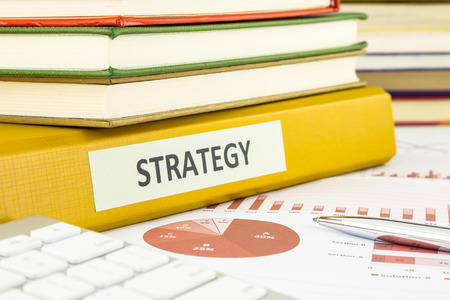 Binder of business strategy documents with graph analysis and budget plan