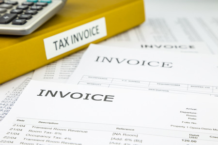 Binder of tax invoice documents with bills and business invoices on background