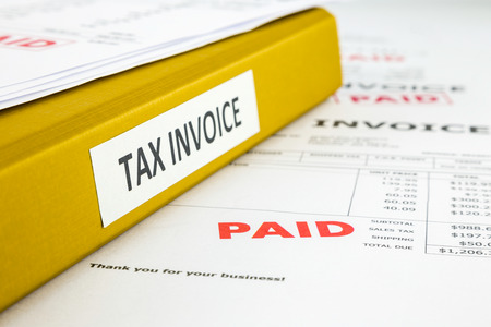Binder of tax invoice documents with bills, business receipts and payment of invoices, focus on word paid photo