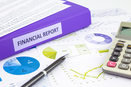 summarized: Purple binder of financial report place on graphs and charts  analysis or business reports, concept to budget management