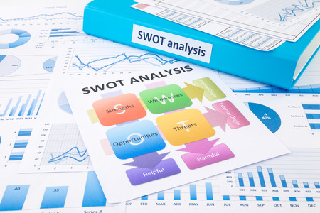 Blue binder, SWOT analysis chart and graph reports for business planning and evaluation