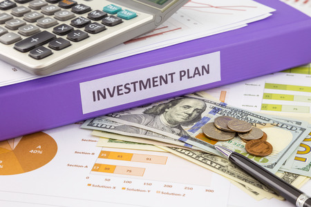 Purple binder of investment plan place on money and financial graphs reports, concept for saving fund and budget management 写真素材