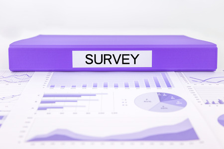 Purple document binder with survey word place on graphs, charts and marketing reports Stock Photo
