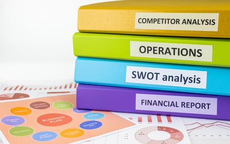 swot: Colorful document binders: SWOT, competitor analysis, operation and financial report place on graph analysis and business plan chart, concept to business plan management