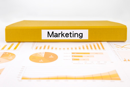 place of research: Yellow document binder with marketing word place on graphs and charts of market trend research