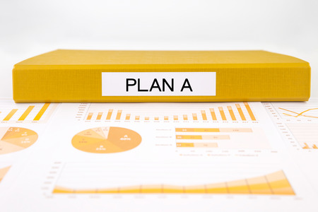 yellow document binder with plan a word place on graphs and charts