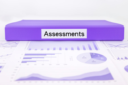 assessments: Purple document binder with assessments word place on graphs, charts and data analysis of business evaluation Stock Photo
