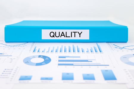 assessments: Blue document binder with quality word place on graphs, charts and business evaluation reports. concept for management plan